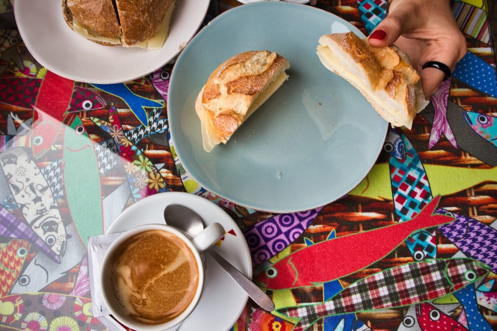 portuguese breakfast bread roll with cheese and coffee served on a colourful table cloth