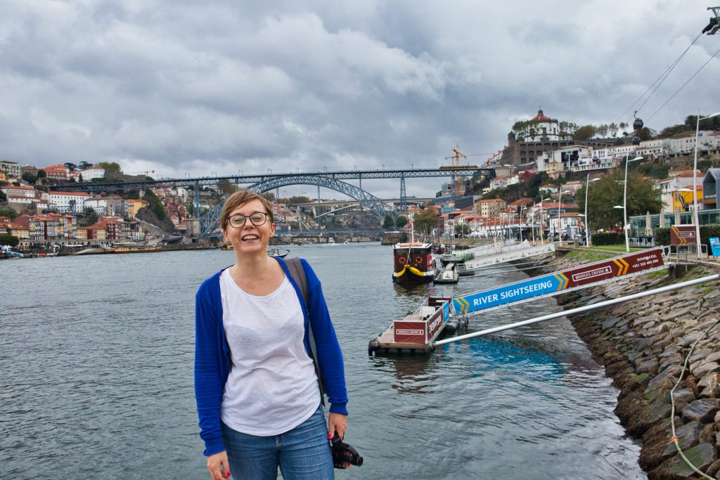 joanna horanin stands at the river bank in porto, portugal on a very cloudy and rainy day