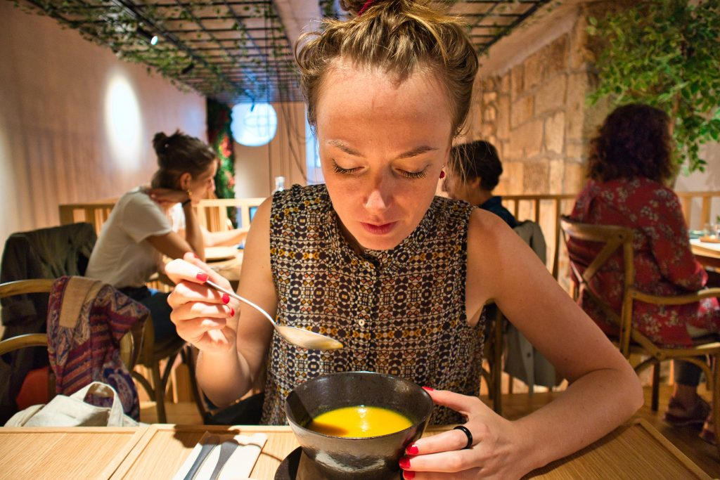 a girl eating a soup in a cosy restaurant