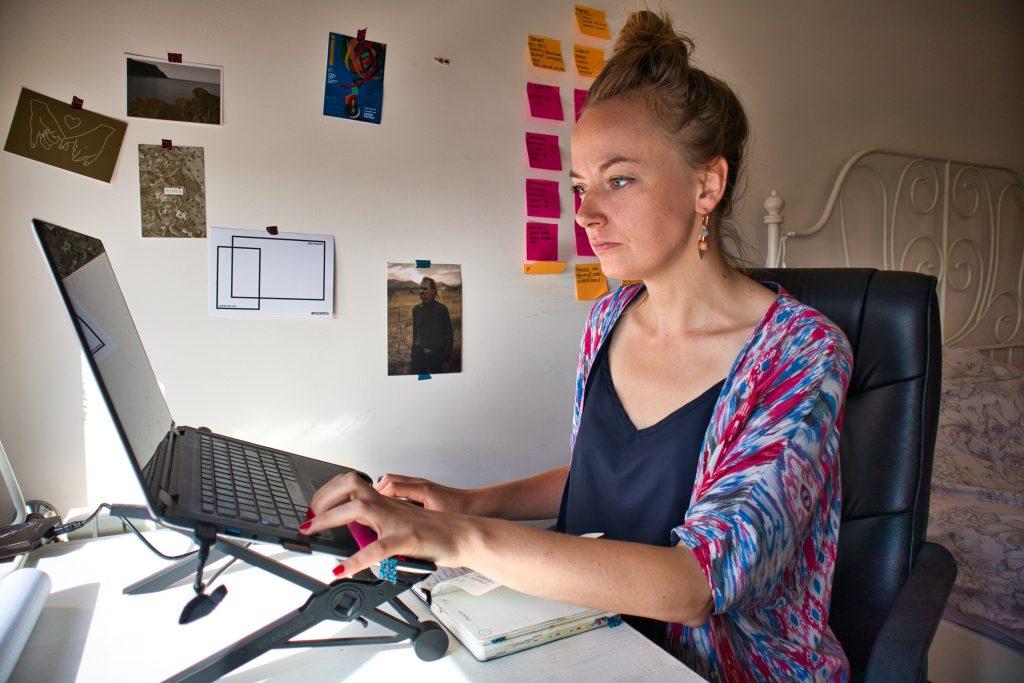 a girl in a colourful jumper sits in her room and works on her laptop