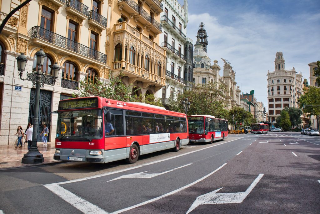 red bus on the street of valencia with white buildings in the back
