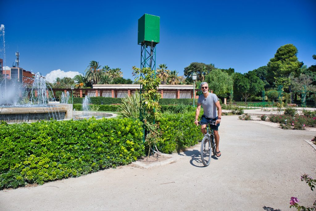 a man cycles in a park near a fountain in valencia spain