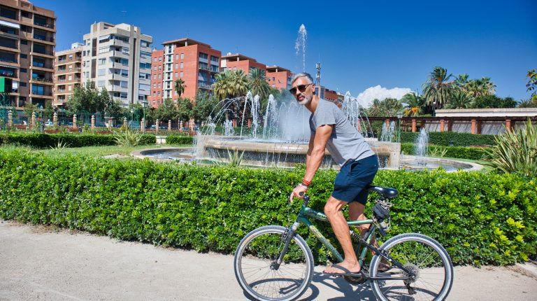 a man cycling in a park near a fountain in Valencia, Spain