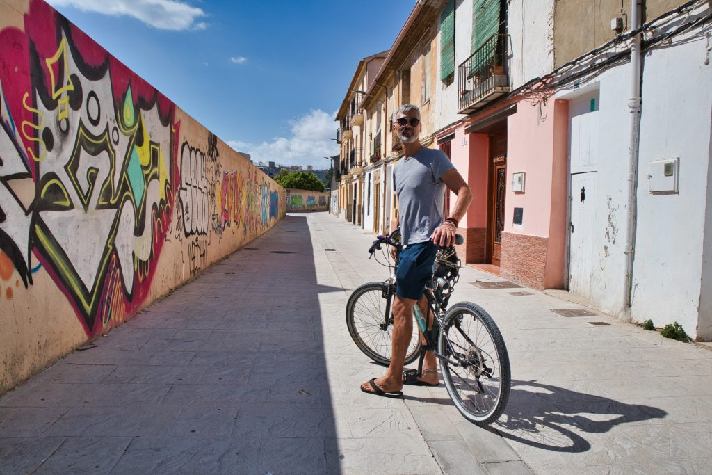 a man on a bike stands in a small side street in valencia spain
