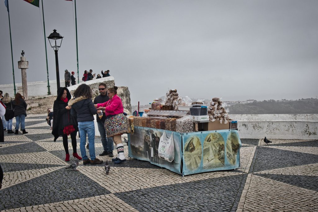 an older lady dressed in seven skirts selling nuts in nazare