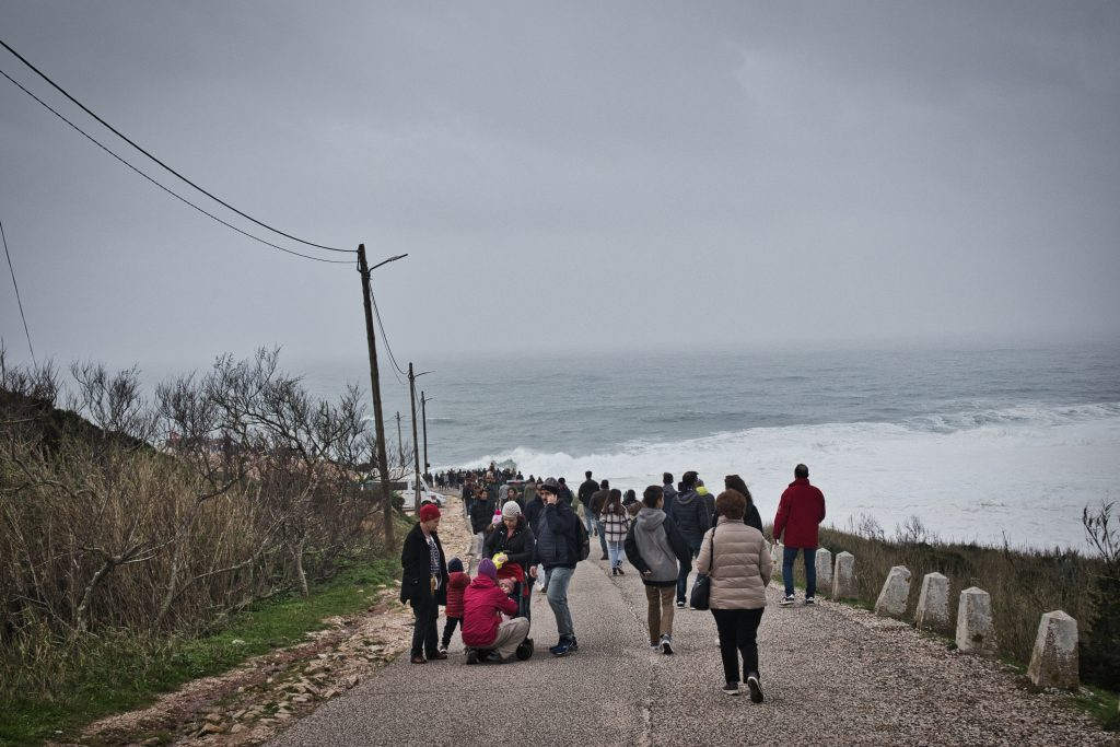 crowds of people walking to the lighthouse in nazare to watch the waves