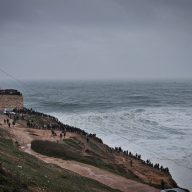 crowds of people standing on a hill and watching the waves in nazare