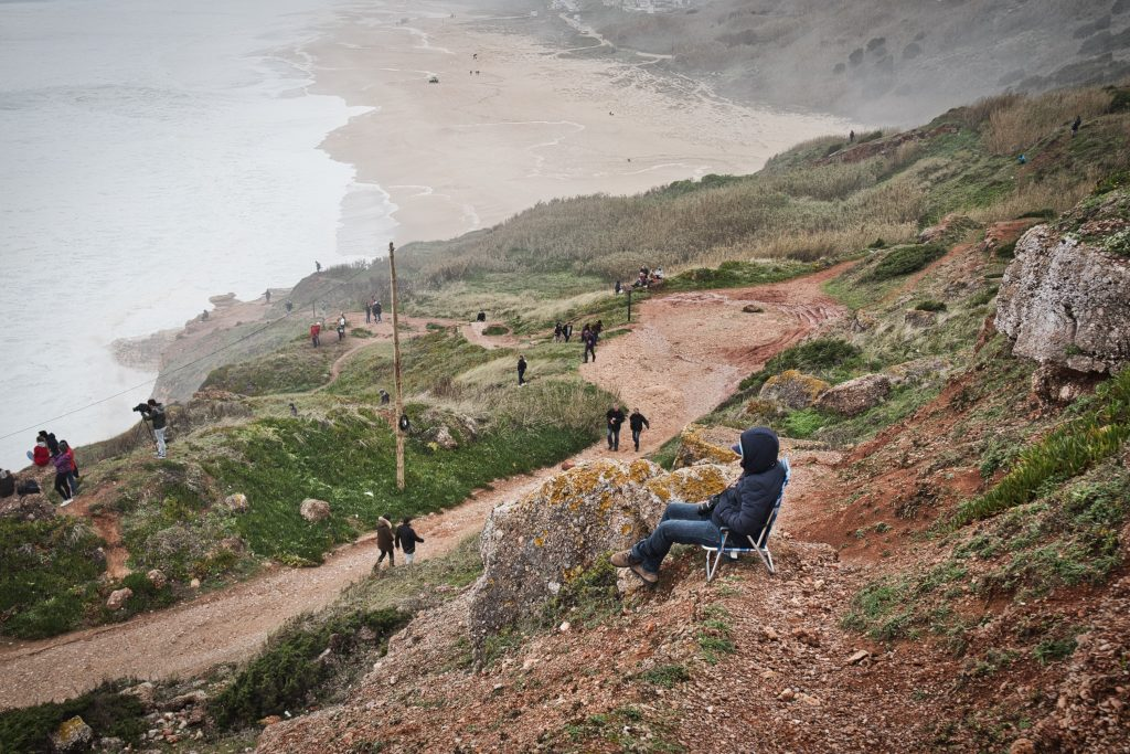 a man sitting on a chair watching waves in nazare, portugal