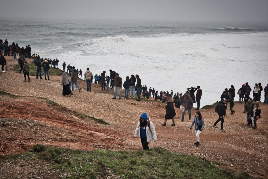 groups of people watching big waves in nazare