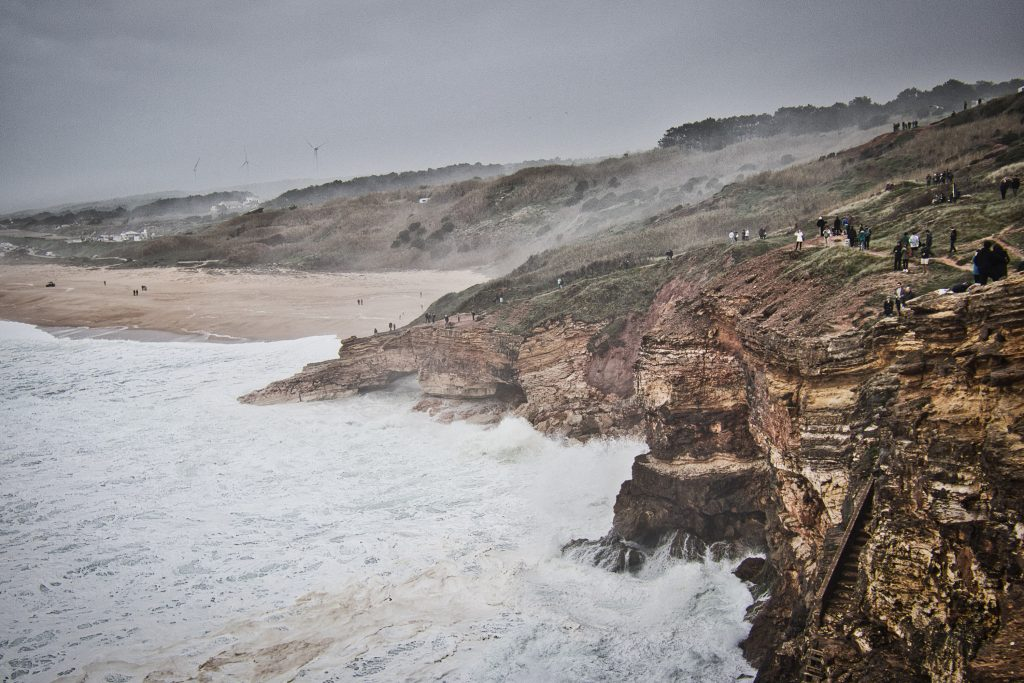 huge waves in nazare hitting the cliffs during a storm