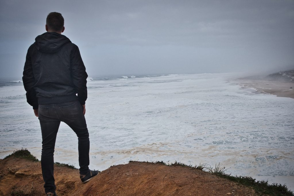a man dressed in black stands on top of a hill and watches the waves in nazare, portugal
