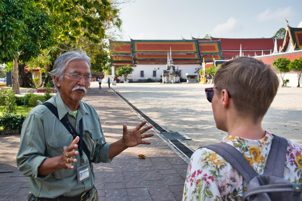 a Thai man and a foreign woman talking in front of a temple in Thailand
