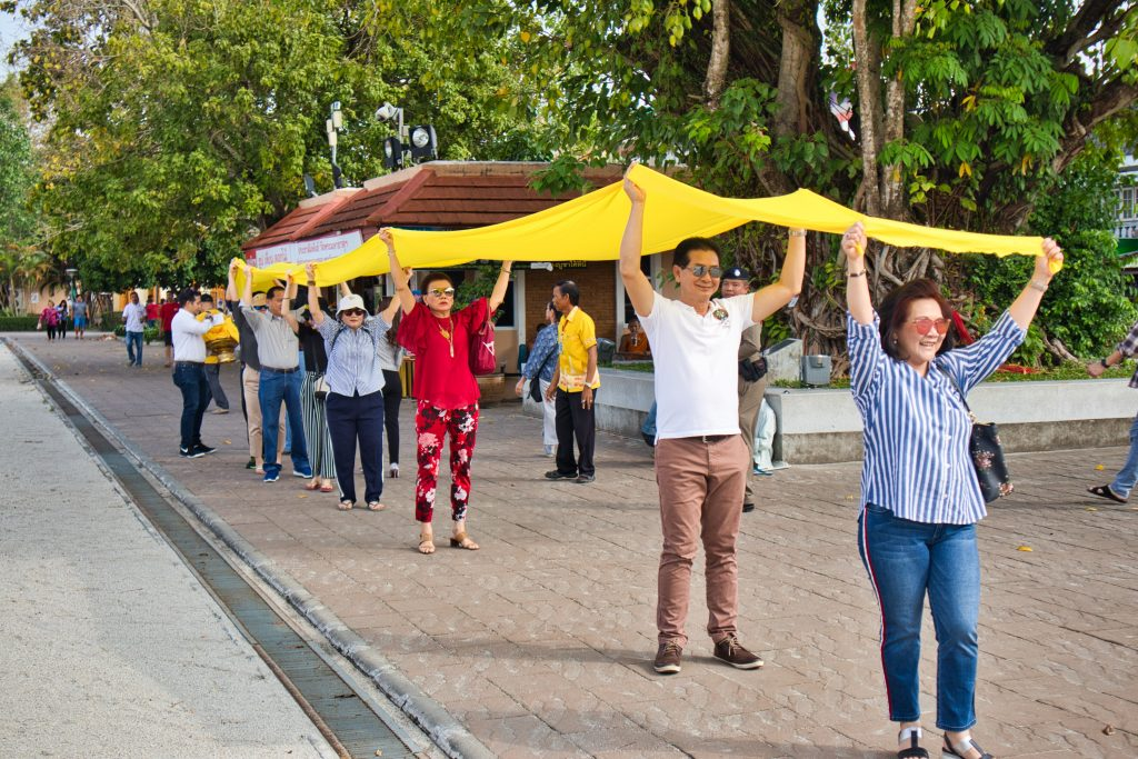 Thai people carrying a long yellow cloth above their heads at a temple in nakhon si thammarat