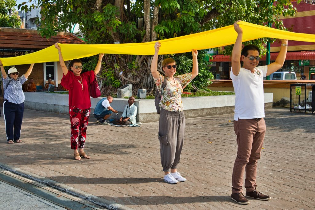 a foreign woman taking part in Buddhist celebration in nakhon si thammarat