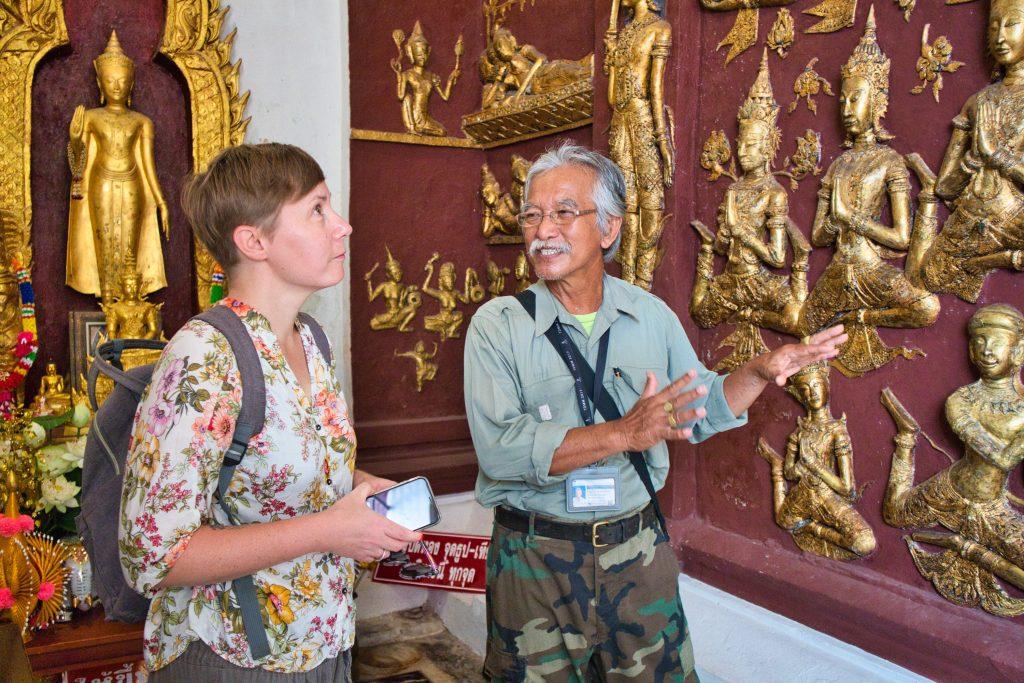 tajski mężczyzna pokazuje turystce z zachodu stiuk przedstawiający sceny z życia buddy