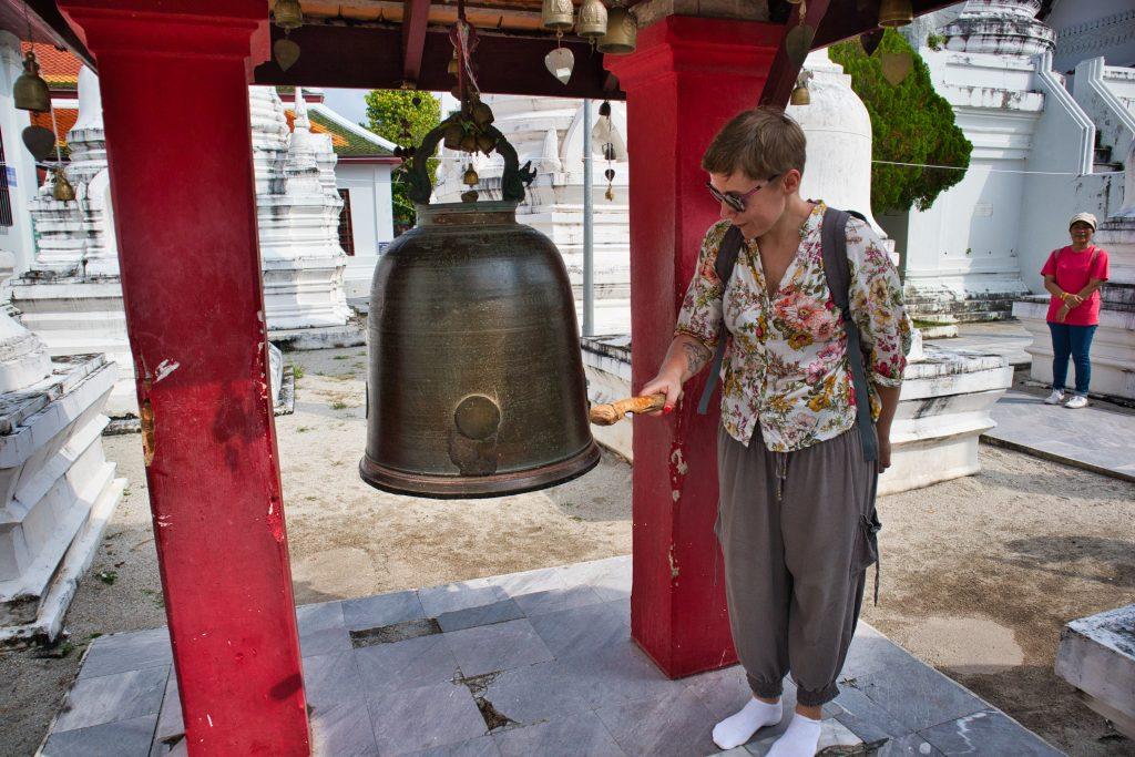 kobieta uderza w dzwon mieszczący się w buddyjskiej świątyni w nakhon si thammarat.