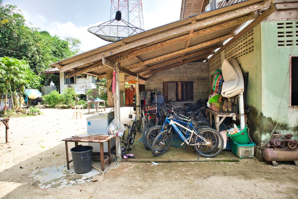 a yard in a thai village. bicycles under a roof