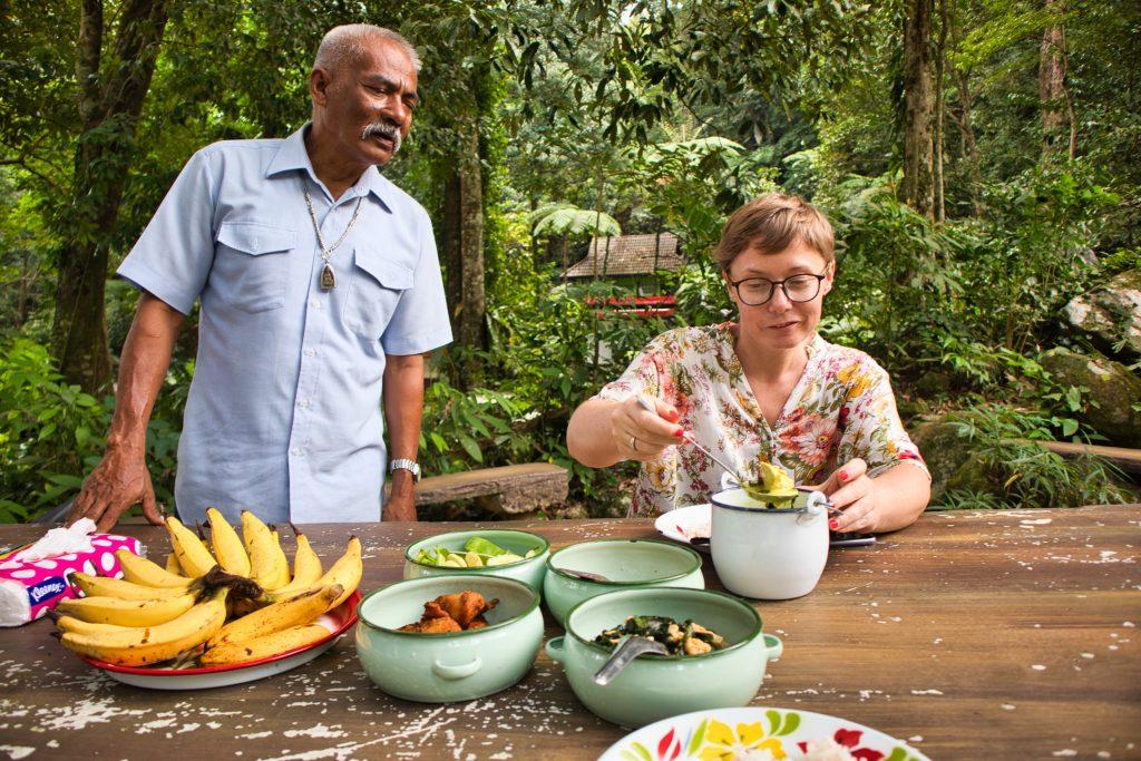 tajski mężczyzna obserwuje turystkę jedzącą tajskie potrawy przy stole w lesie