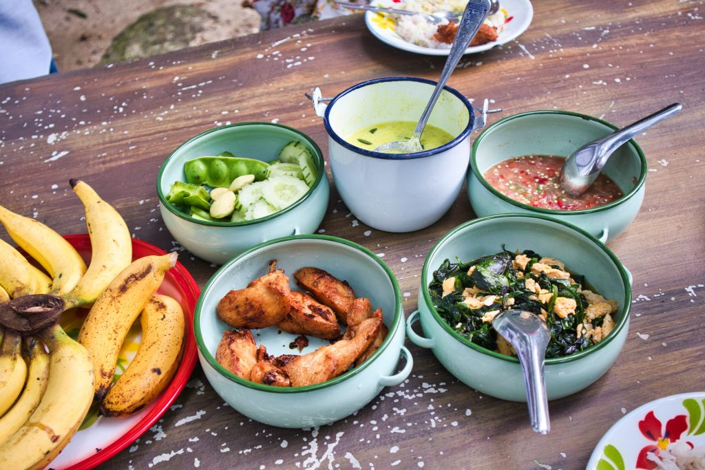Traditional Thai dishes set up on a table in metal containers.