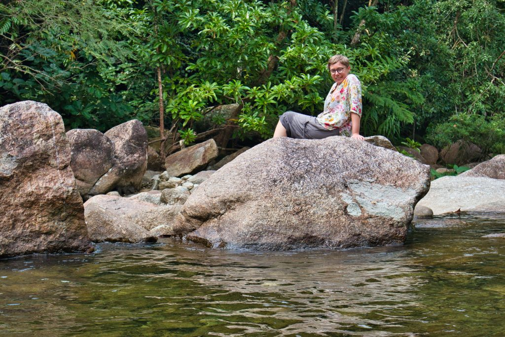 a woman wearing brown trousers and a flowery shirt sits on a rock at promlok waterfall smiling.