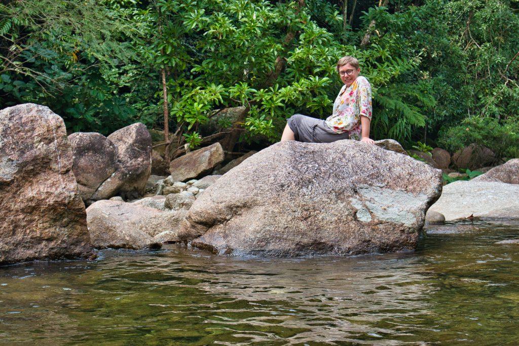 kobieta ubrana w brązowe spodnie i kwiecistą bluzkę siedzi na skałach w promlok