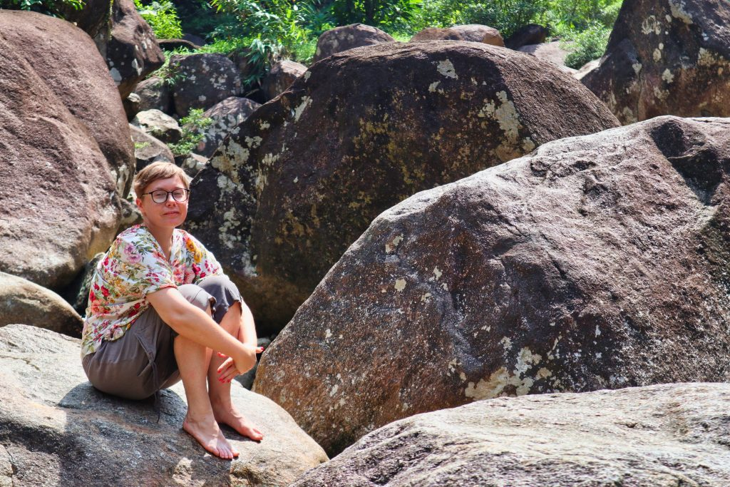 a woman sitting on a rock at promlok waterfall