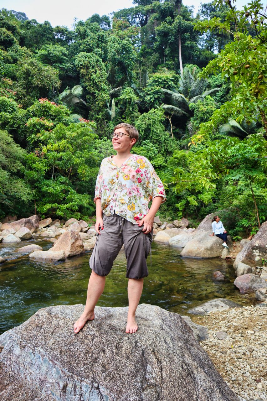a woman dressed in brown trousers and a flowery shirt stands on a rock at the promlok waterfall smiling.