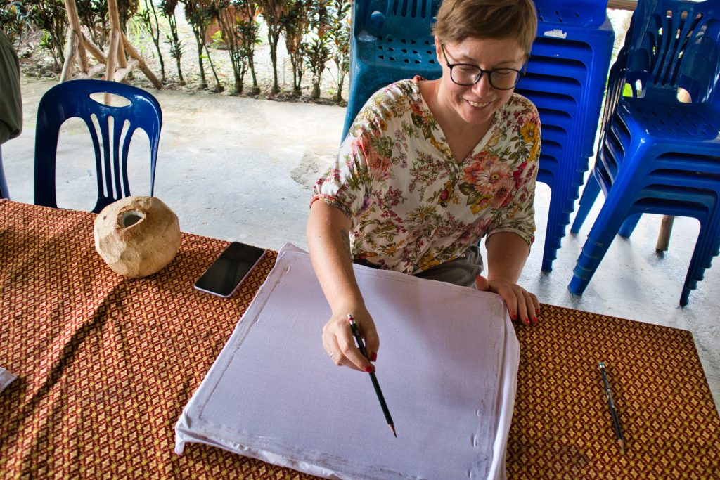 a woman drawing on a canvas in a thai village
