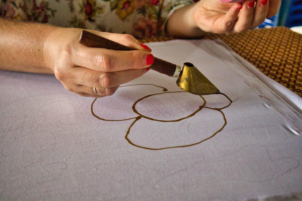 ręka trzymająca narzędzie do produkcji batiku i malująca kwiat