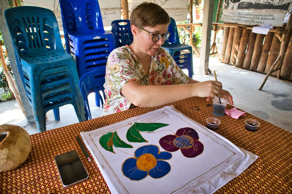 a woman dressed in a flowery shirt sits at a table and draws flowers with batik.