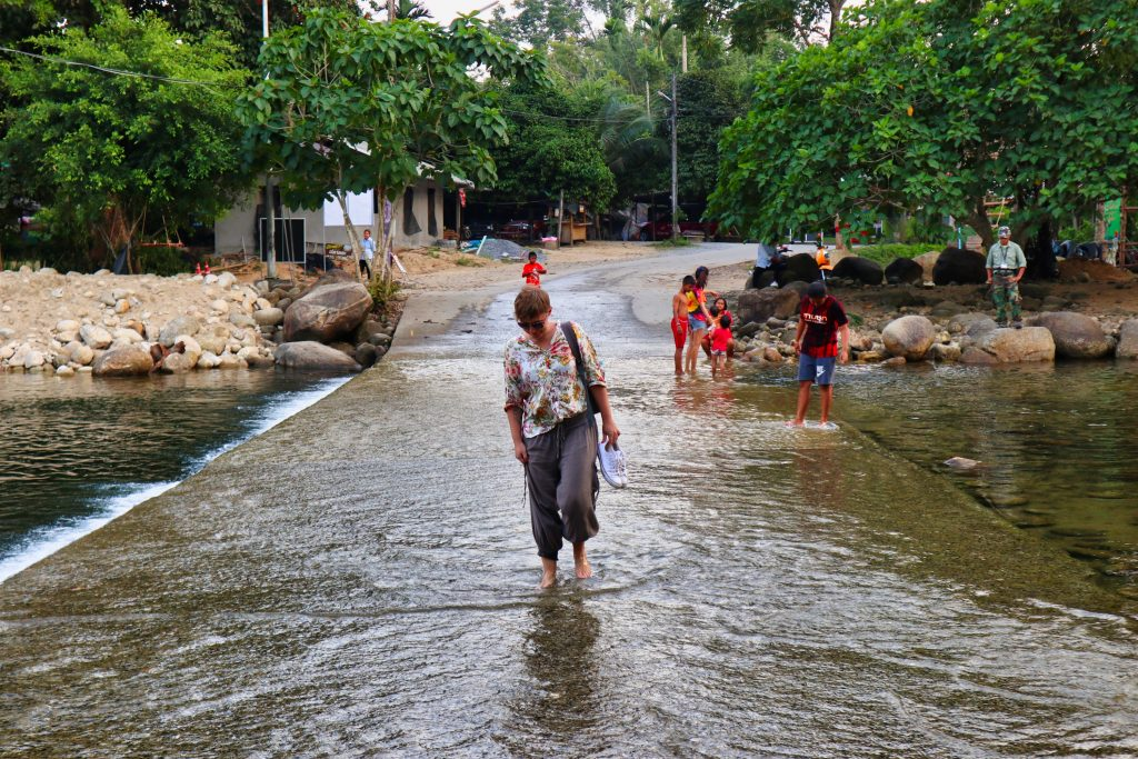 a woman walks through a road cut by a stream in the south of thailand