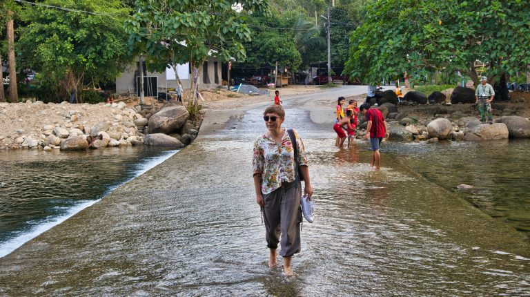 a woman dressed in a flowery shirt walks through the stream in thailand
