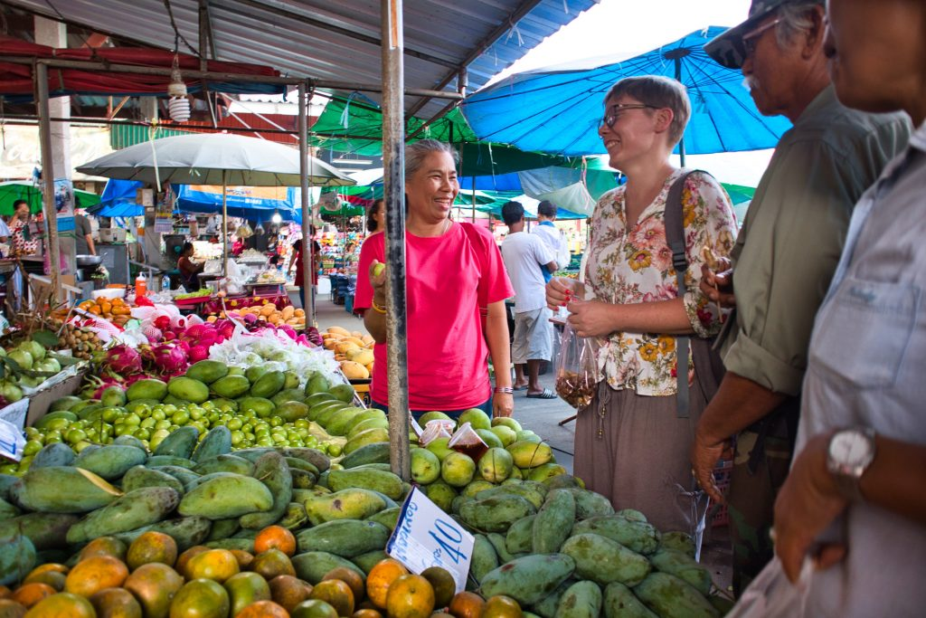 a woman in a flowery shirt talking to a Thai lady at a local market in Promlok.