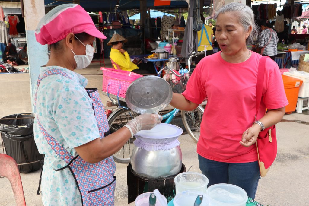 two Thai women at a local market talking about Thai desserts