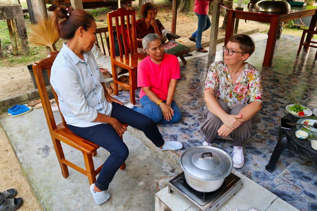 Dwie tajskie kobiety rozmawiają z turystką z zachodu siedząc w kuchni i gotując.