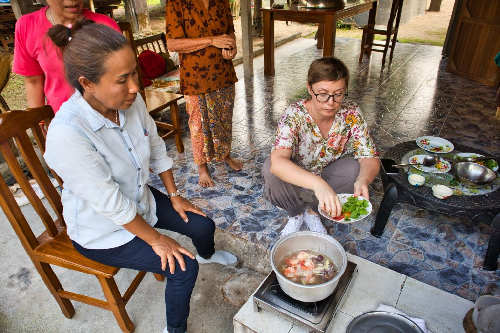 a foreign woman cooking in a Thai home in a Thai village with Thai people watching