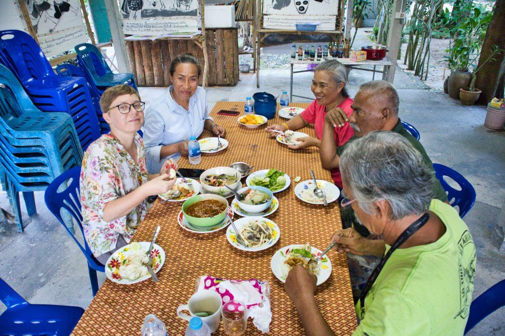 turystka w towarzystwie tajów je tajskie potrawy na tajskiej wsi