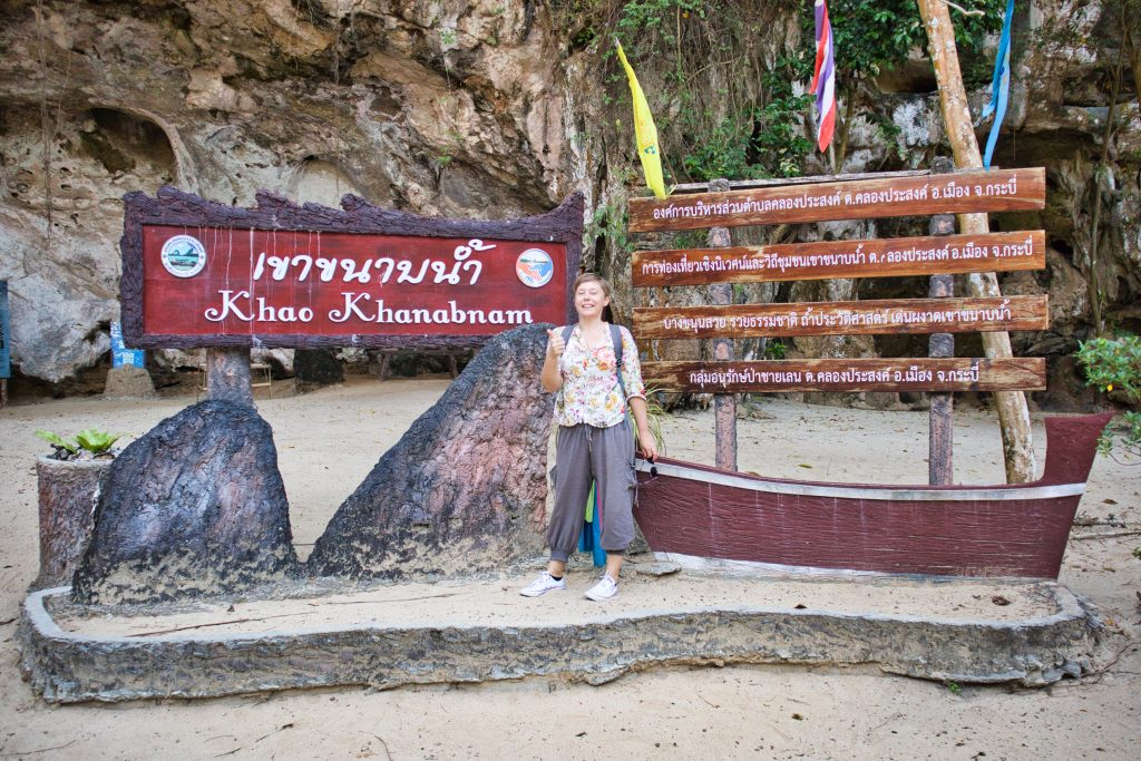 a woman stands in front of a sing at kanabnam cave, krabi province