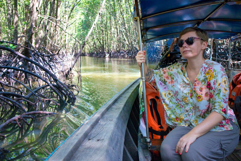 A woman sitting in a long tail boat sailing through mangrove forest in krabi, thailand.