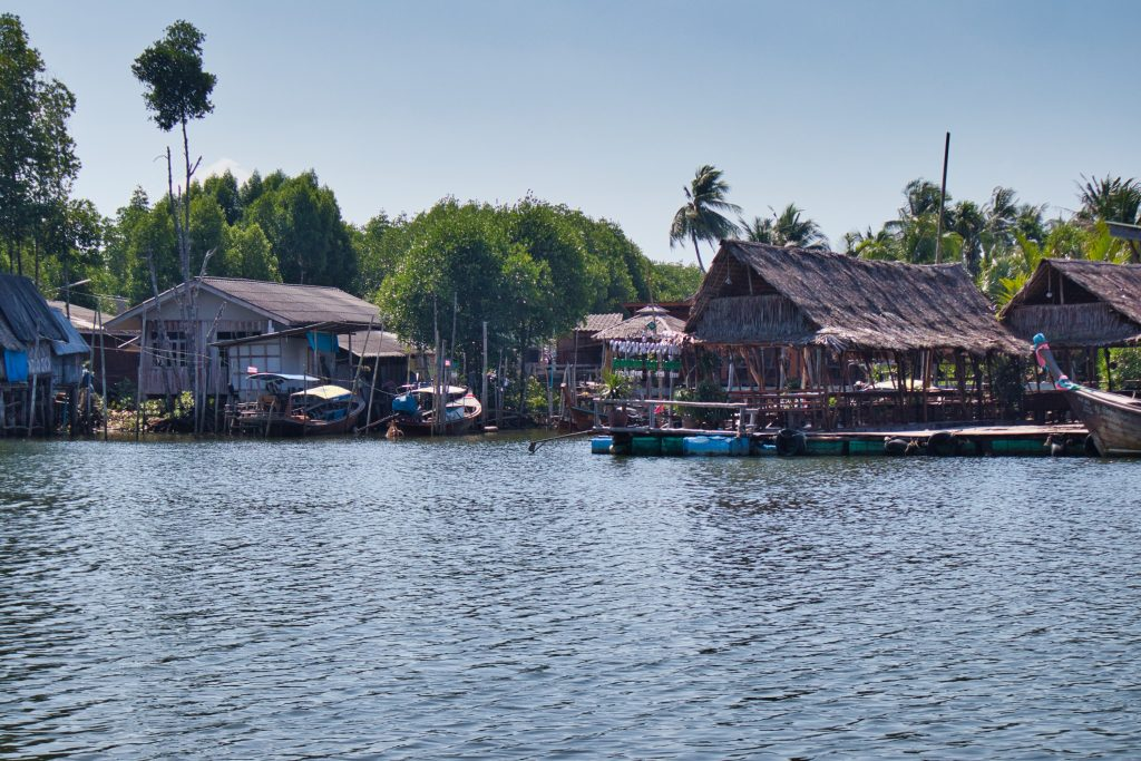 huts seen from a long tail boat on a river in krabi, thailand.