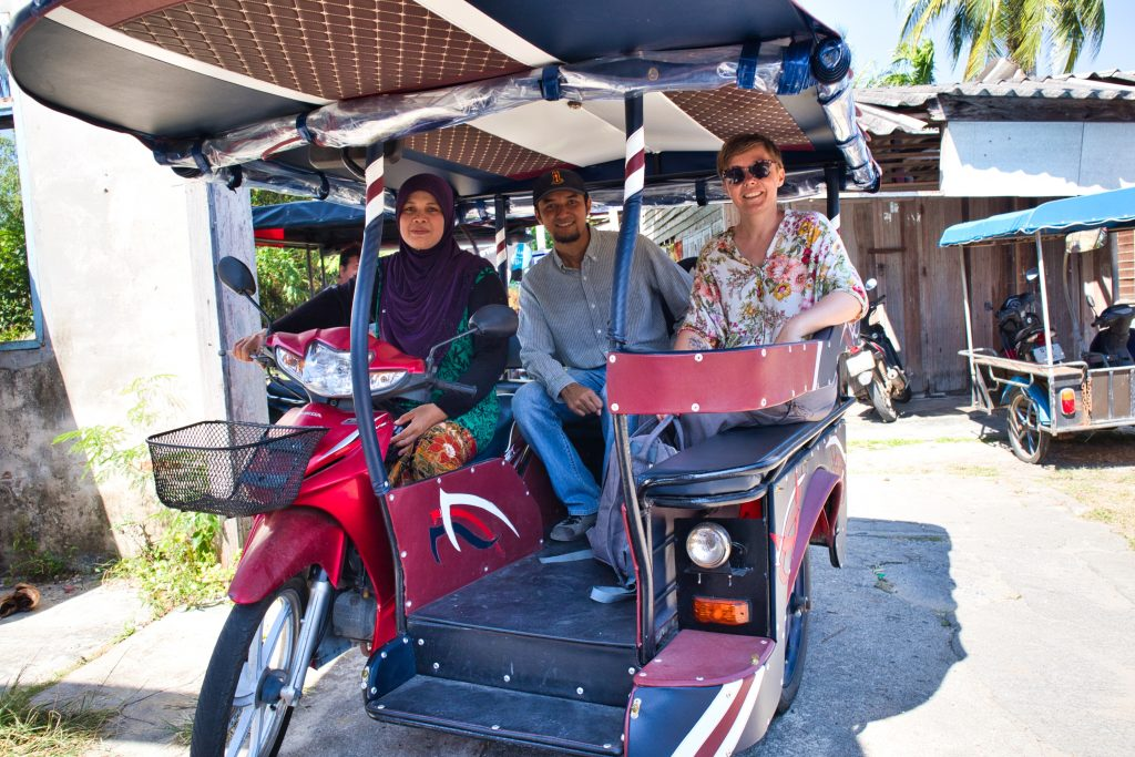 a muslim woman driving a rickshaw with two passangers in krabi, thailand.
