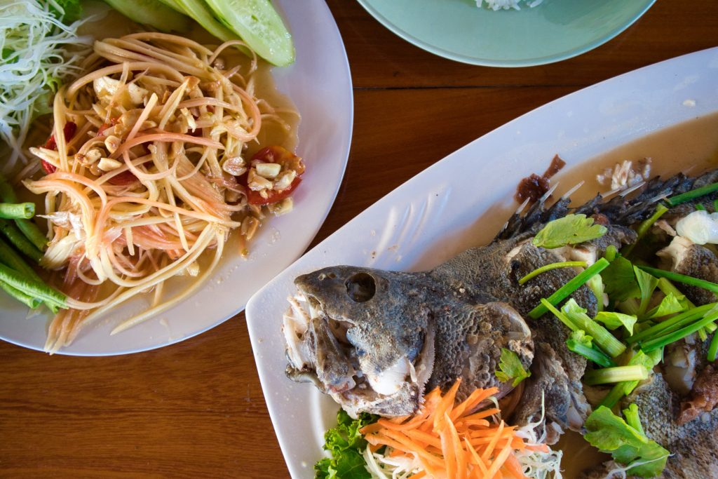 papaya salad and fish on a plate in a restaurant on koh klang, thailand.