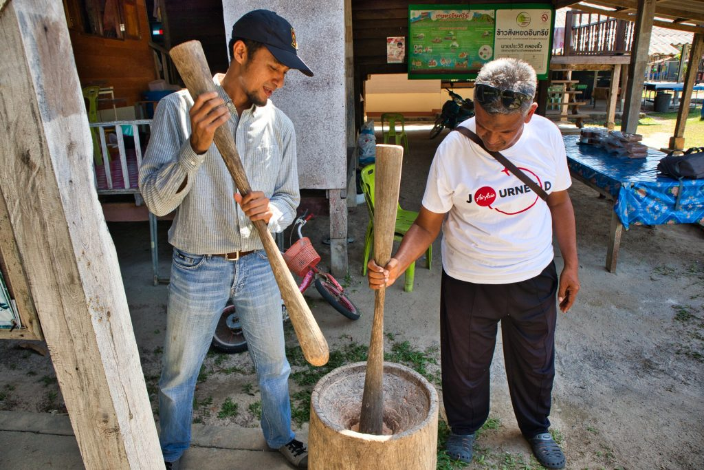 two Thai men are making rice with old tools.