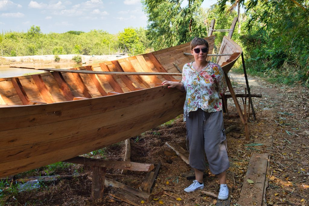 a tourist woman checks out a long tail boat in a workshop in koh klang thailand.