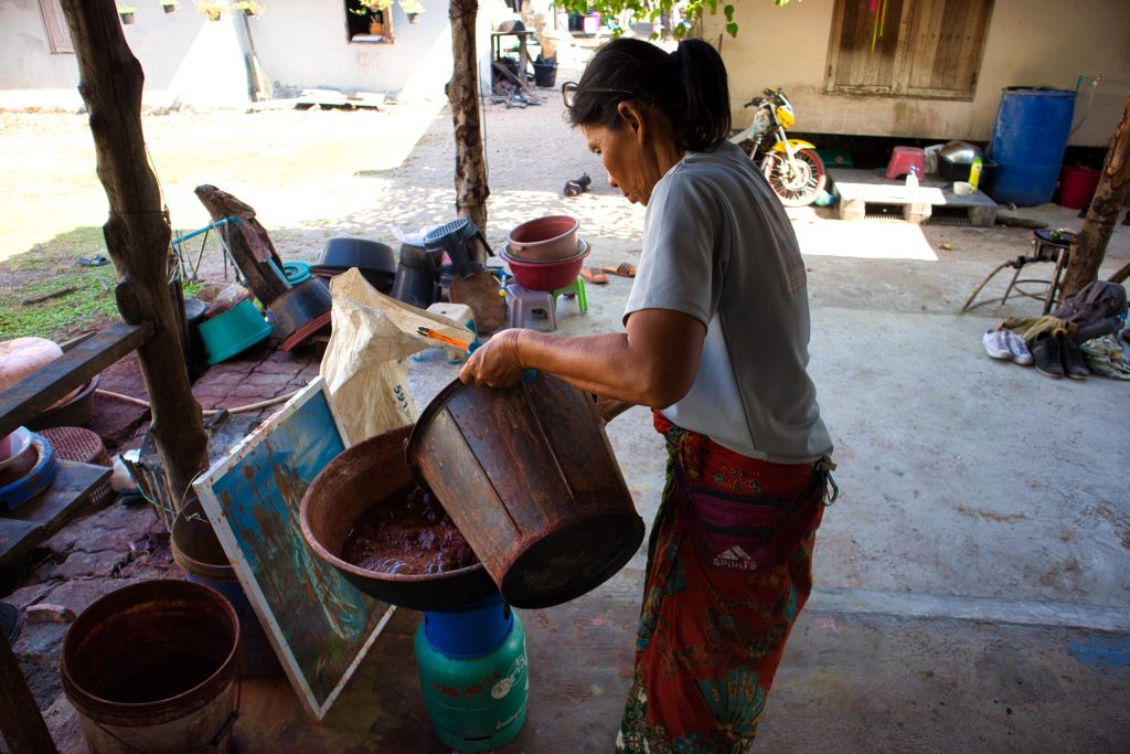 a thai woman is making dye using natural ingredients. she is holding a plastic bucket and pouring water in a bowl. thailand, krabi, koh klang.