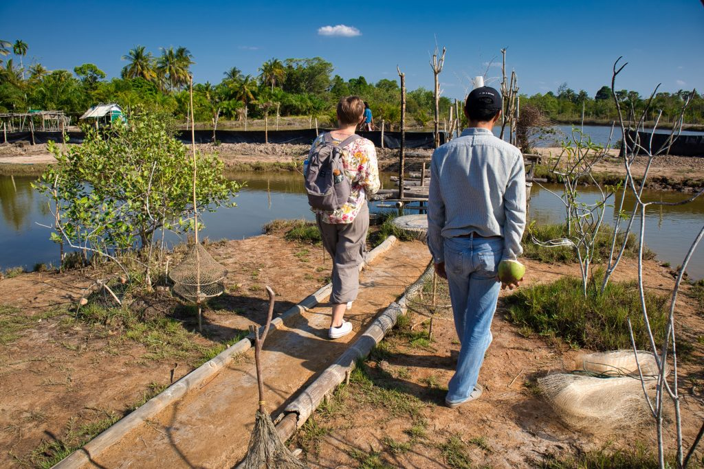 a man and a woman walking through a fish farm on koh klang, thailand.