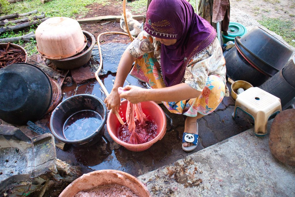 a thai women sitting on the floor washing red material in a red bowl.