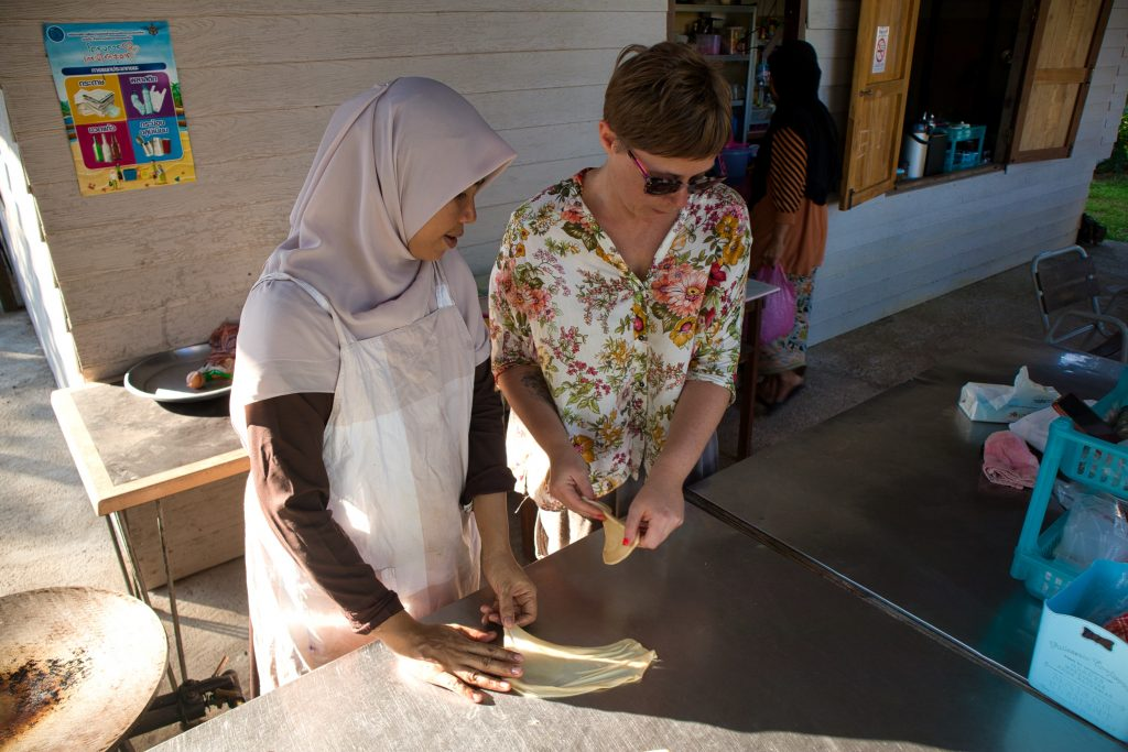 a muslim woman and a foreign woman are making roti together in koh klang.