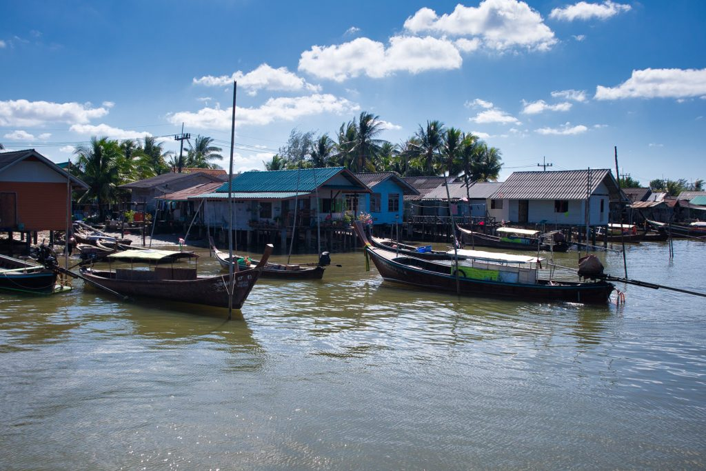 boats standing at huts on stills on a river in koh klang, thailand.
