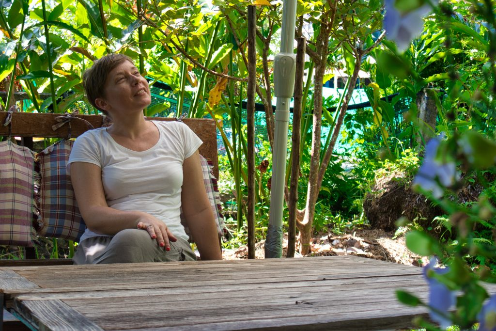 a woman in a white shirt sitting on a wooden bench among green trees. she looks up and smiles a little.
